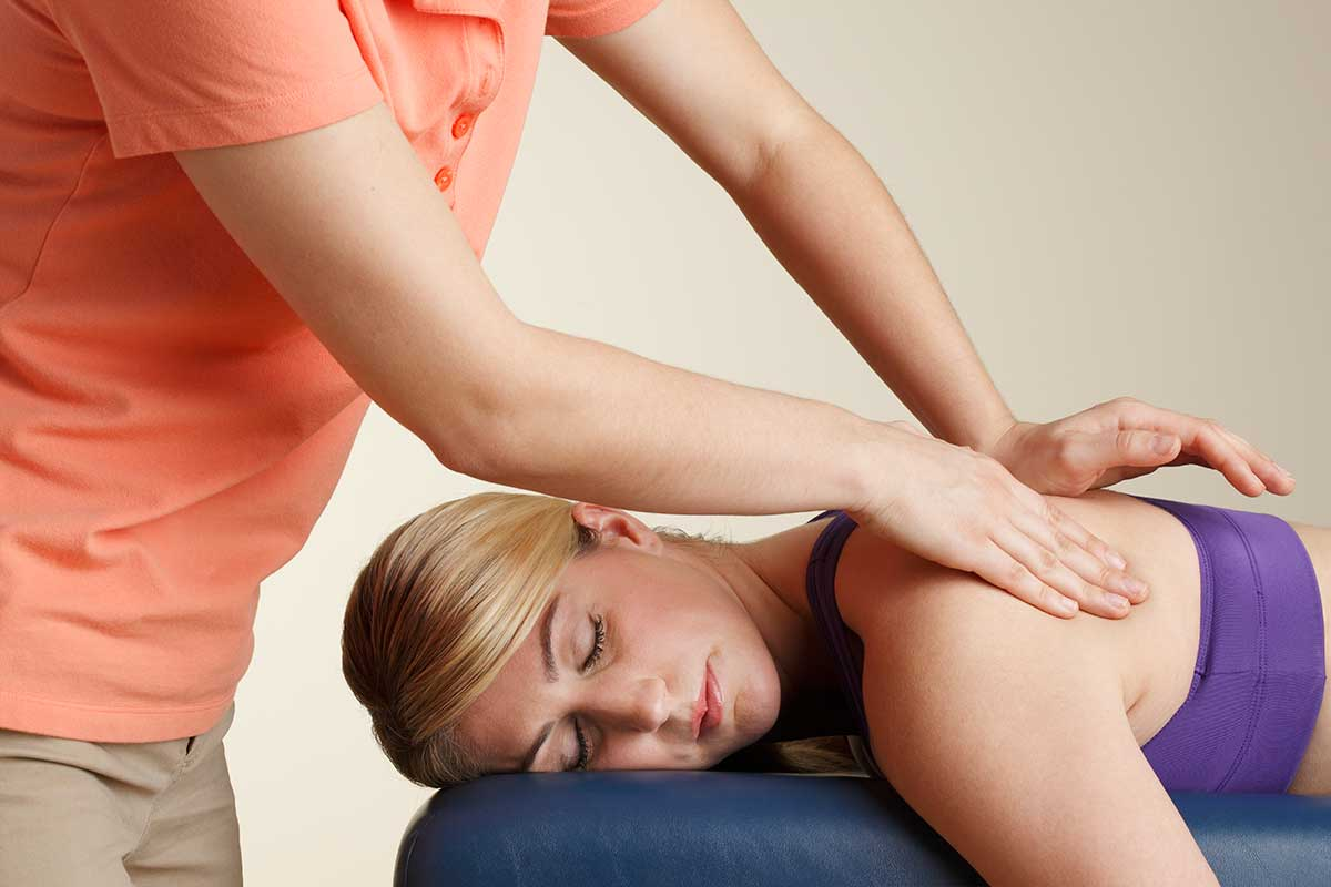 Physical therapist massages a female patient