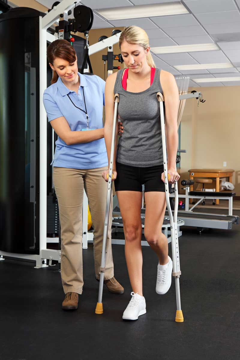 Physical therapist instructing female patient on proper use of crutches