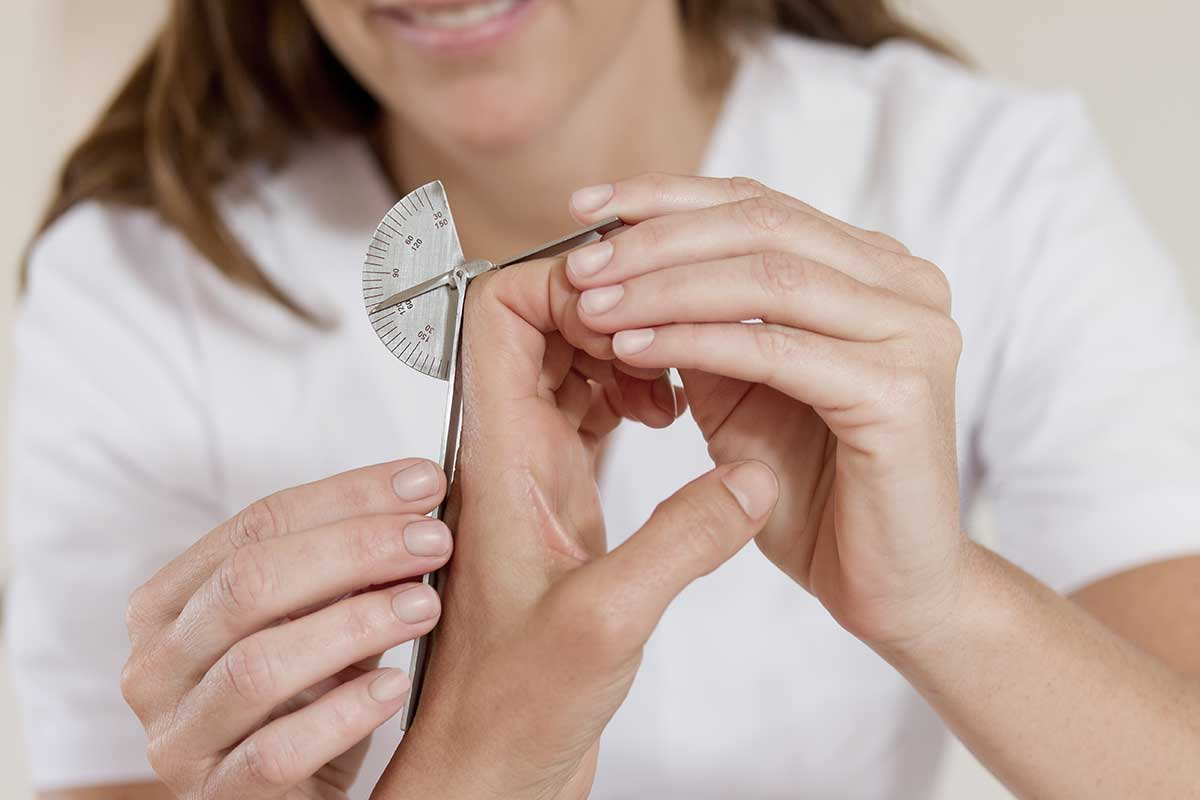 Occupational therapist mesuring patients range of hand motion